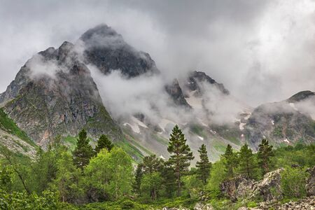 Cloudy weather with clouds over the beautiful mountains of the Caucasus. Rocks Orlenok. Arkhyz. Russia