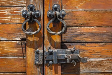 Antique wooden door with bronze handles and a lock close up. Tbilisi. Georgia