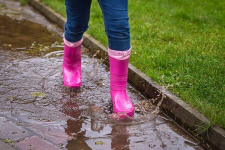 Girl wearing rubber boots standing in a dirty puddle on a summer day. Happy childhood. Having fun outdoors Stok Fotoğraf