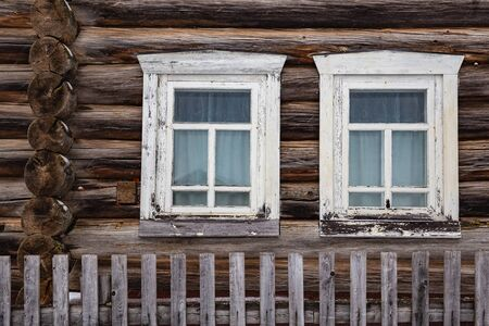 Two windows in white wooden frames of an old wooden log house and a fence. Village Kimzha, Arkhangelsk region. Russia Stok Fotoğraf