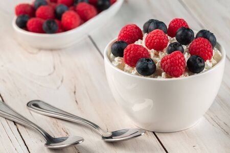 Natural cottage cheese or curd with raspberries and blueberries in a white ceramic bowl on a wooden background. Diet and healthy eating concept Stok Fotoğraf