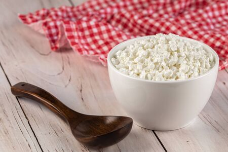 Natural cottage cheese in a white ceramic bowl with wooden spoon and red napkin on a wooden background. Diet and healthy eating concept