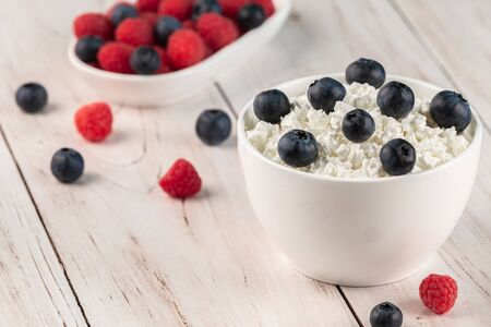 White ceramic bowls with cottage cheese and fresh berries on wooden table. Diet breakfast. Healthy eating concept Stok Fotoğraf