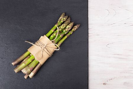 Green asparagus wrapped in paper and tied with a rope on a slate dish on a white wooden background. Healthy eating concept