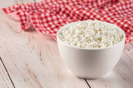 Natural cottage cheese in a white ceramic bowl with wooden spoon and red napkin on a wooden background. Diet and healthy eating concept. High quality photo