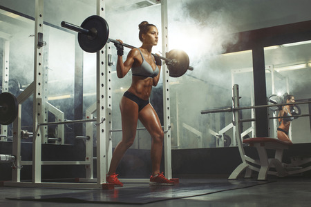 pesas: Mujer de levantamiento de pesas en el gimnasio