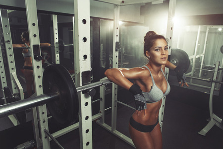 Woman resting after lifting barbells Stock Photo