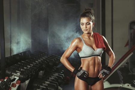 mujeres fitness: Mujer descansando durante el ejercicio en el gimnasio