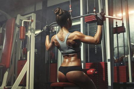 pesas: Mujer contratada en el simulador en el gimnasio