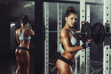 1 woman only: athletic young sexy girl sets weight on barbell in the gym