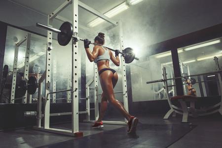 athletes: sexy jeune femme de repos dans le gymnase et se appuyant sur la ligne d'halt�res