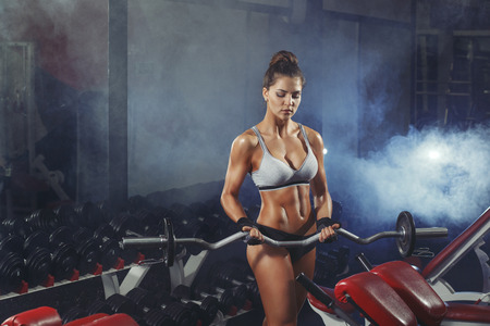 hard working woman: Young sexy woman training with barbell in the gym on smoke background