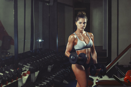 photo of athletic young girl doing a fitness workout with dumbbells in the gym Standard-Bild