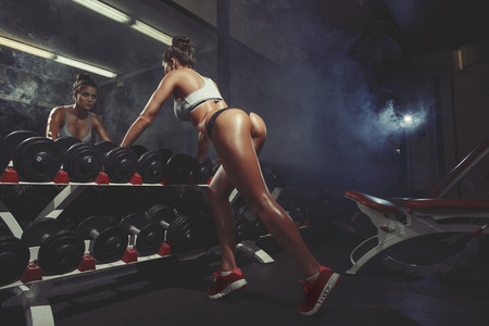 squat: sexy young woman resting in the gym and leaning on row of dumbbells