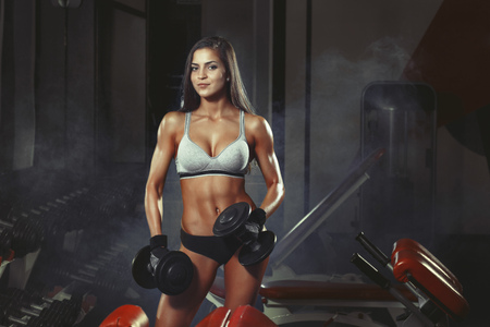hard working woman: photo of athletic young girl doing a fitness workout with dumbbells in the gym Stock Photo