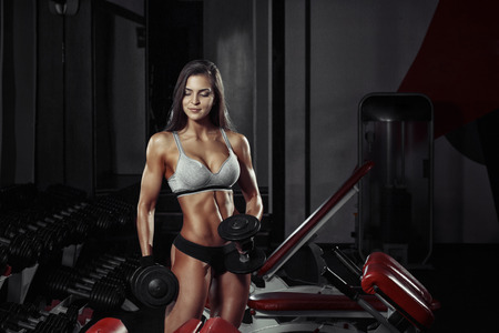 athletic young girl doing a fitness workout with dumbbells in the gym Banco de Imagens
