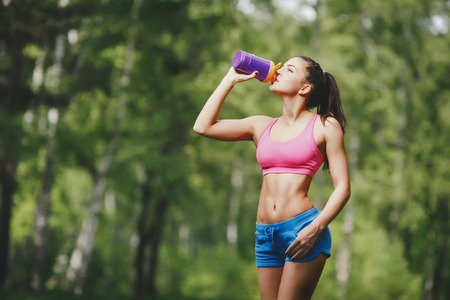 Fitness woman drinking water after running at park Thirsty sport runner resting taking a break with water bottle drink outside after training. Beautiful fit sporty caucasian girl. Banco de Imagens - 42301253