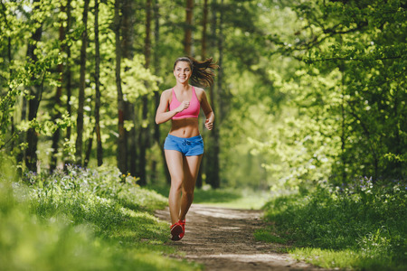 fitness girl running on forest trail and smiling. beautiful woman runs in park