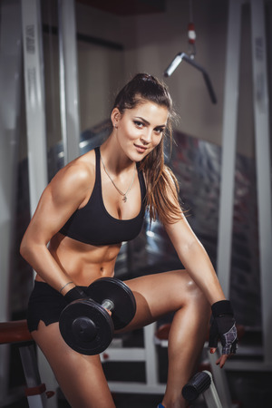 'flat stomach': Sexy sporty girl with perfect body with dumbbells workout in the gy Stock Photo