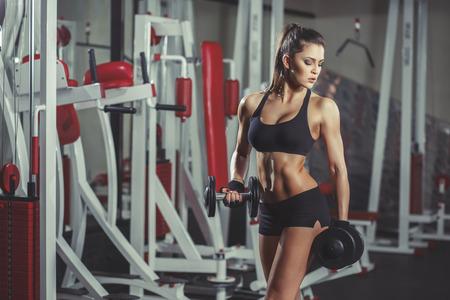 abdomen plano: Muchacha deportiva atractiva con la carrocería perfecta con pesas ejercicio en el gimnasio Foto de archivo