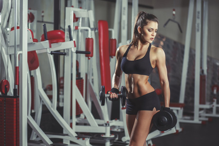 Sexy sporty girl with perfect body with dumbbells workout in the gym Standard-Bild