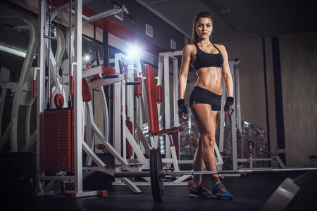 Sporty woman in the gym with exercise equipment and barbell