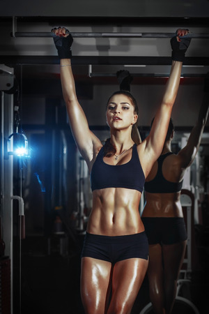athletic fitness  sexy girl pulls up on bar in the gym