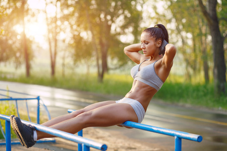 situps: beautiful fitness woman doing exercise on bars sunny outdoor. Sporty girl doing sit-ups on bars outdoors Stock Photo