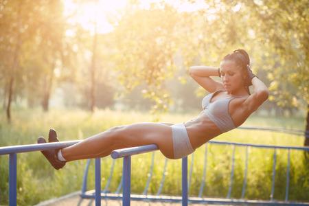 belle femme de fitness faire de l'exercice sur les barres de plein air ensoleillé. Sporty girl faire des sit-ups sur les barres en plein air