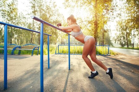 outdoor fitness: fitness woman relax after workout exercises on bars outdoor. brunette fit girl relax after street training