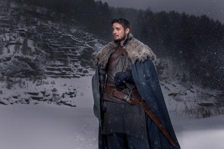 中世の騎士の鎧に剣を持つ