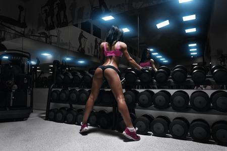 fitness: achteraanzicht van sexy jonge brunette vrouw die in de sportschool en leunend op rij van dumbbells. Fitness meisje in gym in een blauwe sport slijtage