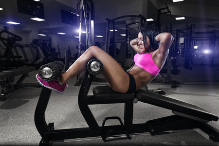 The fitness woman in sport wear with perfect sexy fitness body in gym performing sit up on the bench