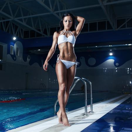 mottled: sexy brunette model in bikini posing at the pool