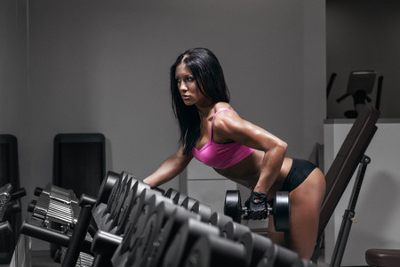 sexy ass: sexy fitness woman in sport wear with perfect fitness body in gym performing back exercises with dumbbell