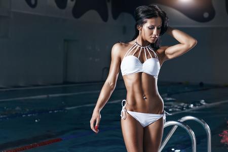 area sexy: Sexy fitness model in bikini in swiming pool area