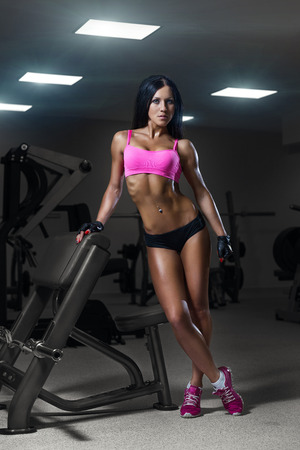 sit up: sexy young girl resting after training. Fitness woman in sport wear with perfect fitness body resting in gym