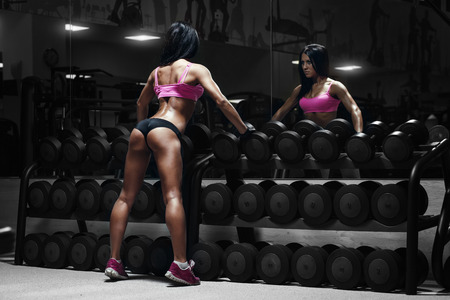back view of sexy young brunette woman resting in the gym and leaning on row of dumbbells. Fitness girl in gym in a blue sport wear Banco de Imagens