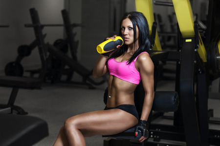 fitness woman in sport wear with perfect sexy fitness body in gym drinking from shaker bottle after training photo