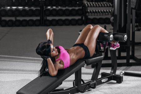 athletic brunette woman doing some crunches in a bench at the gym. Fitness girl sit up in gym