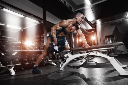 Athlete muscular bodybuilder training back with dumbbell in the gym Stock Photo