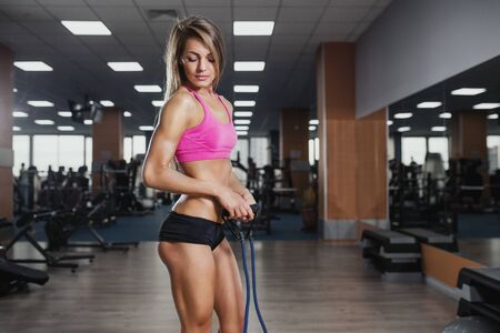 expander: Fitness beautiful woman execute exercise with expander in gym. Stretch Band Stock Photo