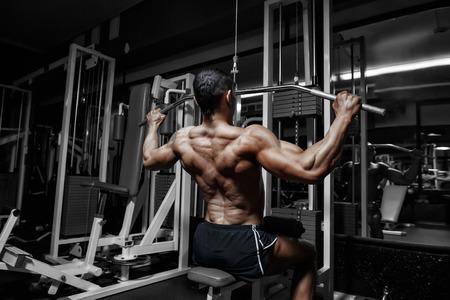bodybuilder: Atleta entrenamiento culturista muscular espalda en el simulador en el gimnasio Foto de archivo