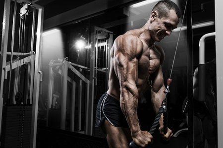 only the biceps: Athlete muscular bodybuilder training back on simulator in the gym Stock Photo