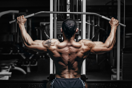 holding back: Athlete muscular bodybuilder training back on simulator in the gym Stock Photo
