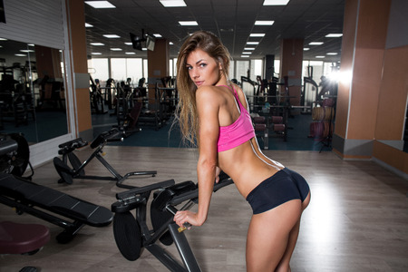 sexy young girl: Sexy young girl resting after squat exercises. Fitness beautiful woman Stock Photo