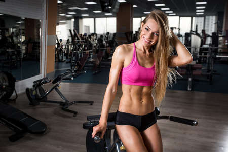 Sexy young girl resting after squat exercises. Fitness beautiful woman Standard-Bild