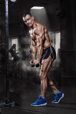 only the biceps: Athlete muscular bodybuilder training on simulator in the gym