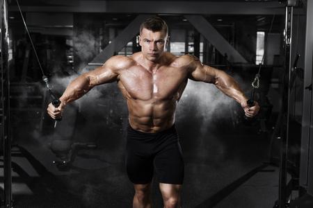 Athlete muscular bodybuilder training on simulator in the gym