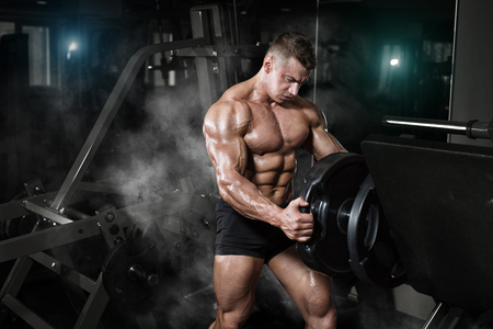 only the biceps: Bodybuilder muscle Athlete training with weight in gym